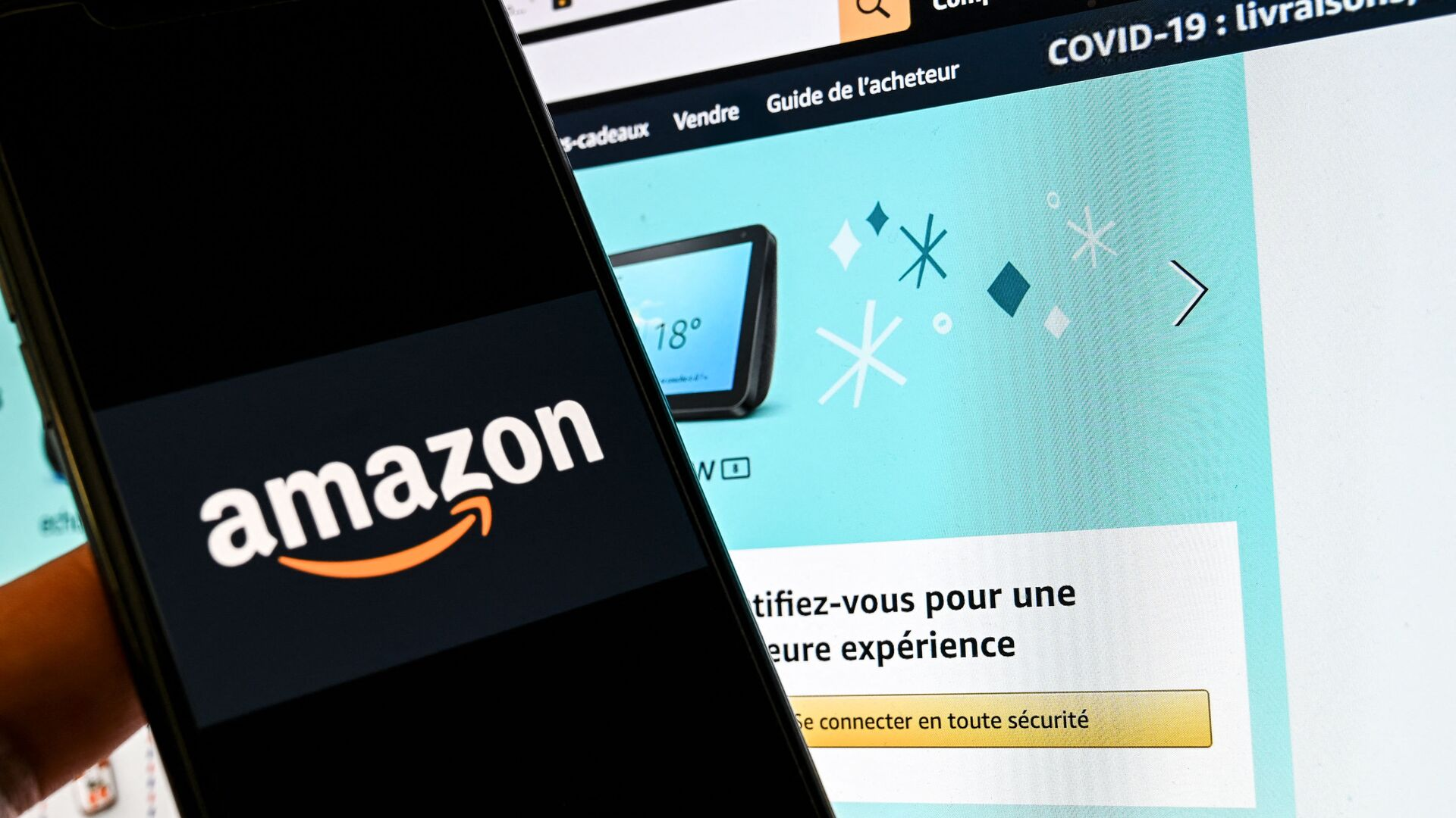 In this photograph taken on November 18, 2020 in Lille, a person poses with a smartphone showing an Amazon logo, in front of a computer screen displaying the home page of Amazon France sales website. - Sputnik International, 1920, 30.07.2021