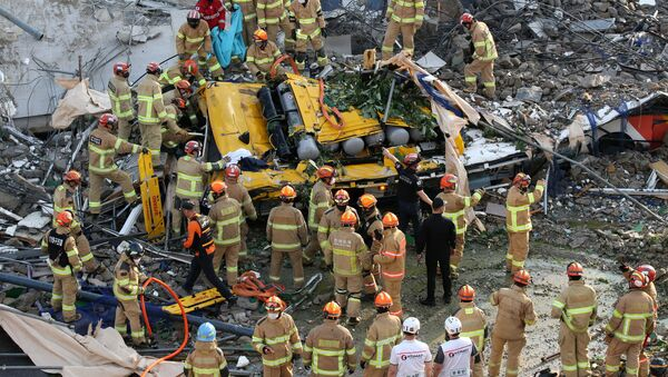 South Korean firefighters search for passengers from a bus trapped by the debris of a collapsed building in Gwangju, South Korea, June 9, 2021. - Sputnik International
