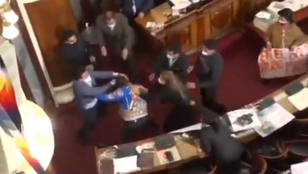 Bolivian lawmakers Antonio Colque (MAS) and Henry Montero (Creemos) trade punches during a tense hearing in Bolivia's Plurinational Legislative Assembly on June 8, 2021. - Sputnik International