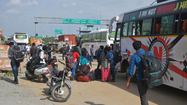 People wait on the outskirts of Bangalore to board buses and return to their home towns on the border of the states of Karnataka and Tamil Nadu, as another lockdown looms to tackle the surge in COVID-19 coronavirus cases on 13 July 2020. - Sputnik International