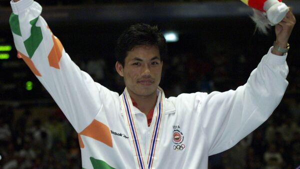 India's Ng-Dingko Singh celebrates on the podium after winning gold in the bantam weight boxing finals at the 13th Asian Games in Bangkok 17 December - Sputnik International