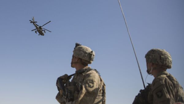 This June 10, 2017 photo released by the U.S. Marine Corps shows an AH-64 Apache attack helicopter provides security from above while CH-47 Chinooks drop off supplies to U.S. Soldiers with Task Force Iron at Bost Airfield, Afghanistan. - Sputnik International