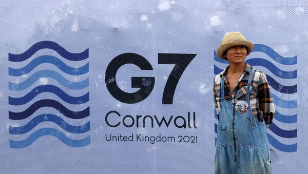 A pedestrian poses for a photograph with a G7 logo outside the media centre at Falmouth, Cornwall on June 10, 2021, ahead of the three-day G7 summit being held from 11-13 June - Sputnik International