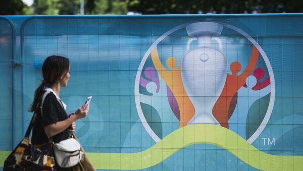 A pedestrian walks past the logo of the UEFA EURO 2020 European Football Championship in Copenhagen, one of the tournament's host cities, on June 10, 2021 - Sputnik International