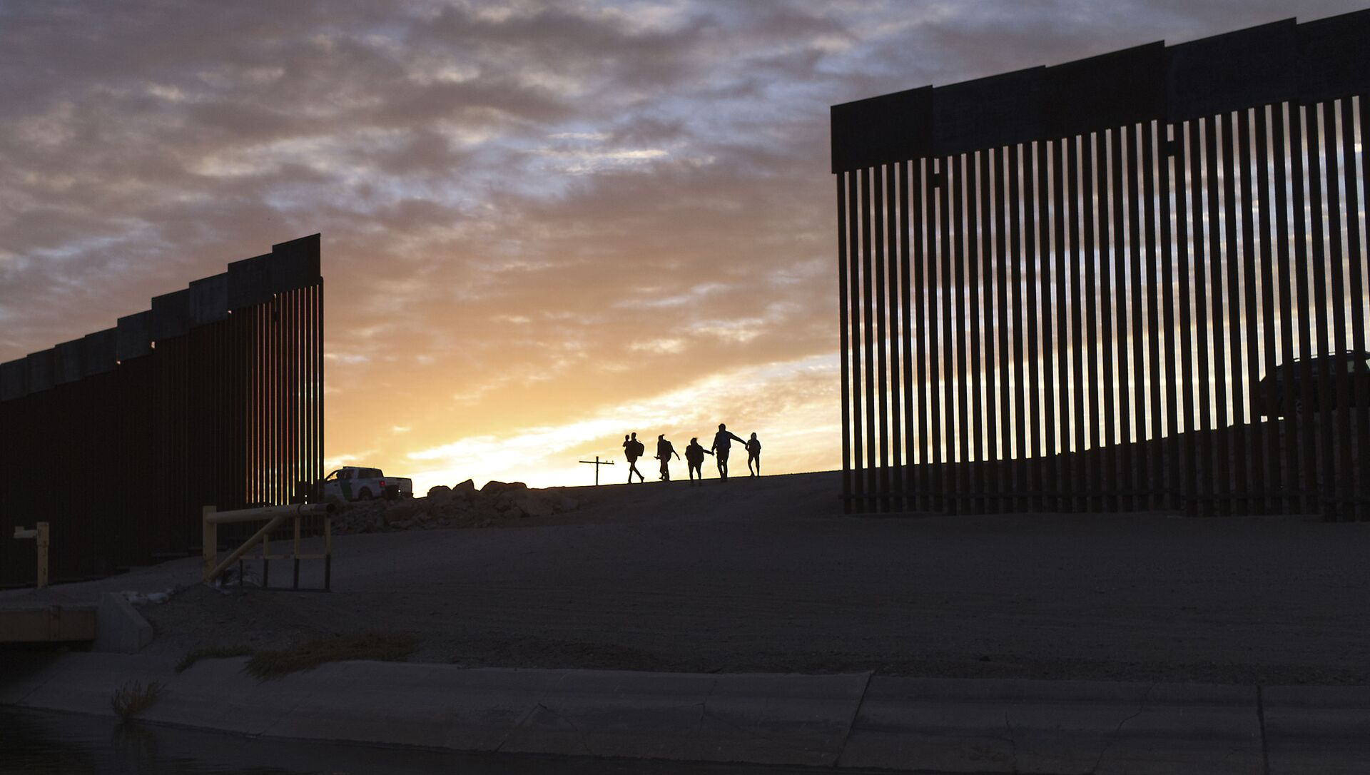 A pair of migrant families from Brazil pass through a gap in the border wall to reach the United States after crossing from Mexico in Yuma, Ariz., Thursday, June 10, 2021, to seek asylum. - Sputnik International, 1920, 11.06.2021