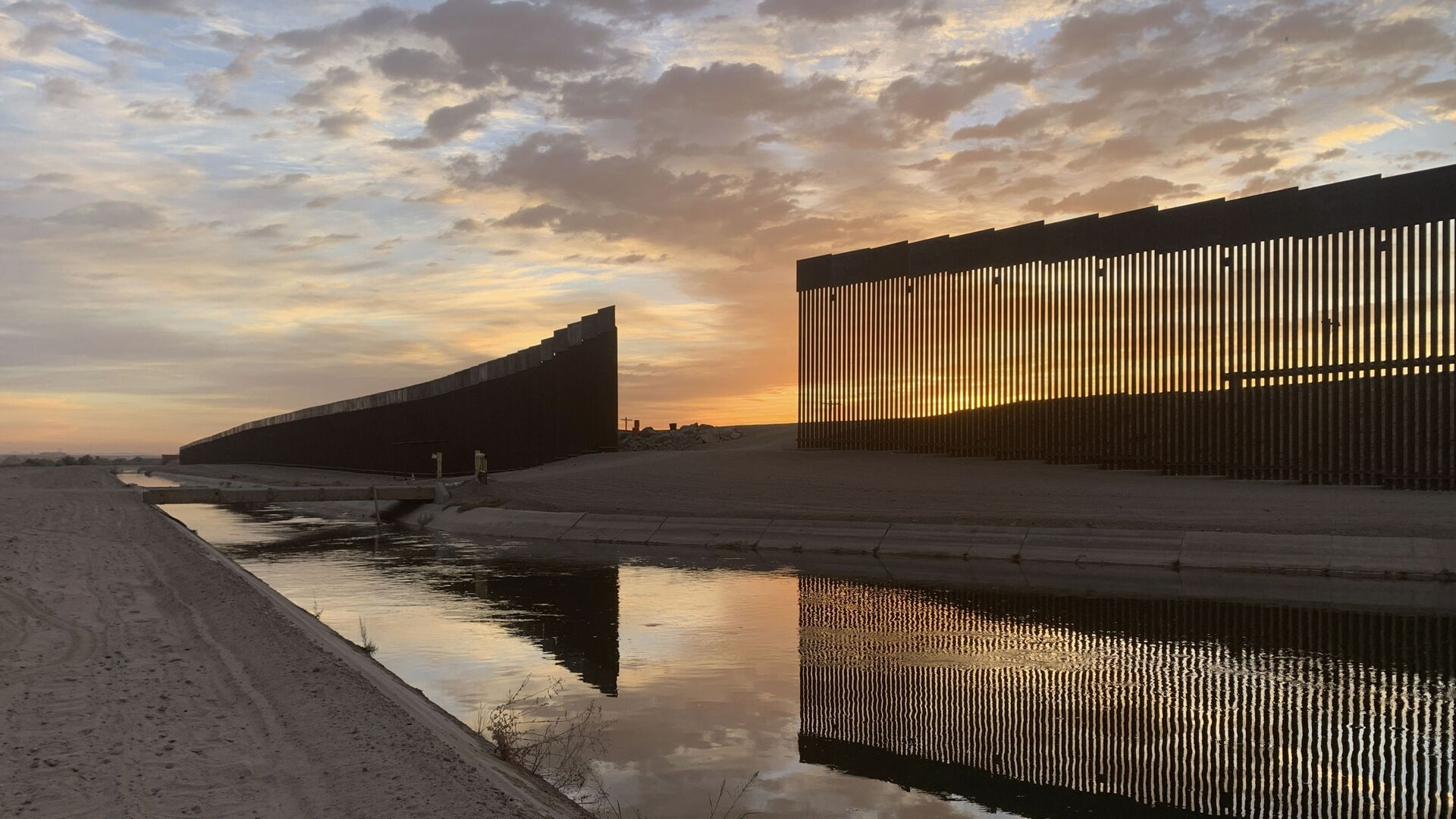 The sun sets above the U.S.-Mexico border wall, seen in Yuma, Ariz., Wednesday, June 9, 2021. - Sputnik International, 1920, 26.09.2021
