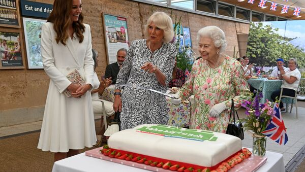 Britain's Queen Elizabeth holds a sword in order to cut a cake next to Catherine, the Duchess of Cambridge and Camilla,  Duchess of Cornwall - Sputnik International