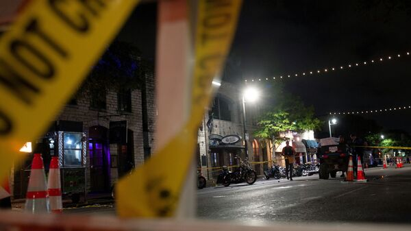 Police investigate the scene of a mass shooting in the Sixth Street entertainment district area of Austin, Texas, U.S. June 12, 2021. - Sputnik International