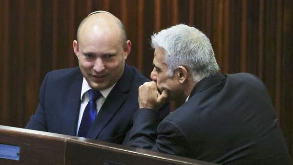 Israel's Yamina party leader, Naftali Bennett (L), smiles as he speaks to Yesh Atid party leader, Yair Lapid, during a special session of the Knesset, Israel's parliament, to elect a new president, in Jerusalem on June 2, 2021. - Sputnik International