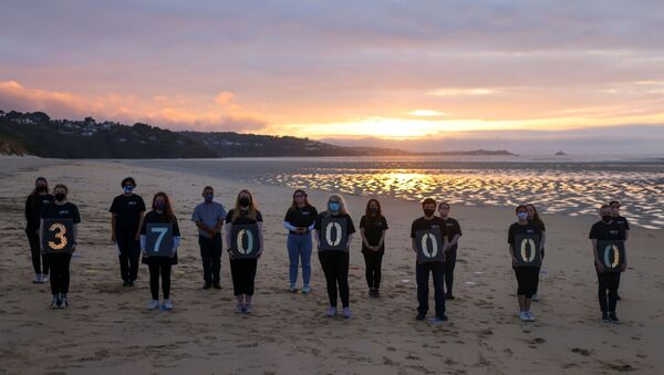 Activists from Crack the Crisis hold a vigil for the people around the world who have passed away due to the coronavirus disease (COVID-19) on the sidelines of G7 summit, at Porthkidney beach near Carbis Bay - Sputnik International