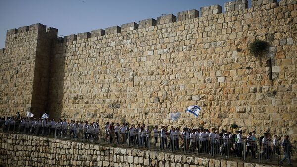 Youths wave Israeli flags during a parade marking Jerusalem Day amid Israeli-Palestinian tension as they march along the walls surrounding Jerusalem's Old City, May 10, 2021. REUTERS/Nir Elias/File Photo - Sputnik International