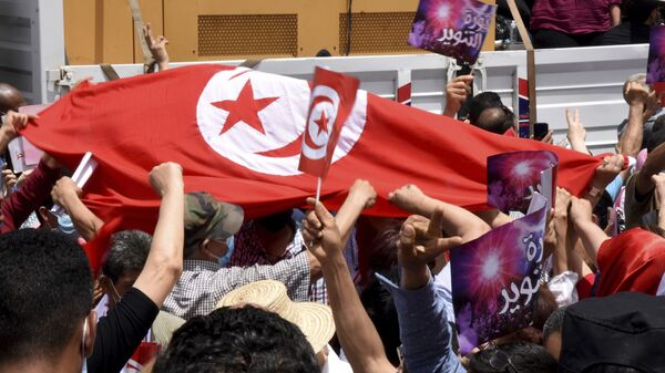 Demonstrators hold a Tunisian flag during a protest in Tunis, Saturday, June 5, 2021. Demonstrators will go to the streets of Tunis on Saturday to protest against the parliament and against the increase of the price in basic products announced this week by the government.  - Sputnik International