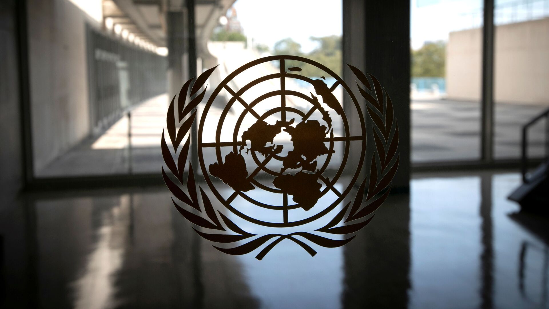 The United Nations logo is seen on a window in an empty hallway at United Nations headquarters during the 75th annual UN General Assembly high-level debate, which is being held mostly virtually due to the coronavirus disease (COVID-19) pandemic in New York, US, September 21, 2020 - Sputnik International, 1920, 21.09.2021