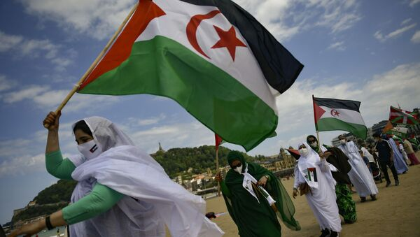 Saharan demonstrator wave their flags as they take part in a rally along the Concha beach support Brahim Gali, leader of the Polisario Front and a Sahara free, in San Sebastian, northern Spain, Sunday, May 30, 2021. Brahim Gali is recovering from COVID-19 in a Spanish hospital. The leader of the Western Sahara independence movement at the heart of a diplomatic spat between Spain and Morocco will appear before an investigating judge in Spain on June 1. - Sputnik International