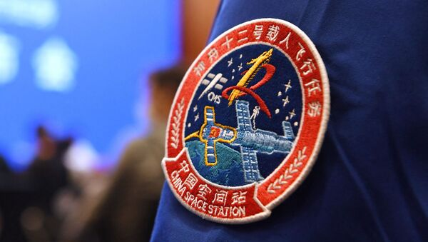 A staff member of the Jiuquan Satellite Launch Centre wears the logo of China's new space station during a press conference about the first crewed mission to the station, scheduled for June 17, at the Jiuquan Satellite Launch Centre in the Gobi desert in northwest China on June 16, 2021. - Sputnik International