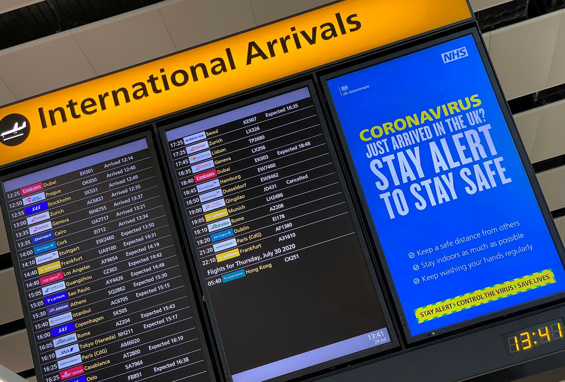 A public health campaign message is displayed on an arrivals information board at Heathrow Airport, following the outbreak of the coronavirus disease (COVID-19), London, Britain, July 29, 2020 - Sputnik International, 1920, 07.09.2021