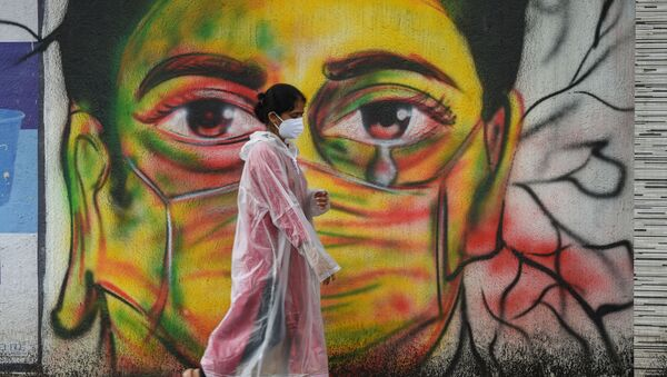 A woman wearing a raincoat walks past a mural depicting a woman with a facemask to spread awareness about the Covid-19 coronavirus, in Mumbai on June 17, 2021 - Sputnik International