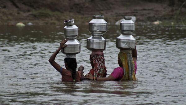 Indian women hold each other as they cross the River Heran after collecting drinking water near Sajanpura village in Chhota Udepur district of Gujarat state, India, Tuesday, Aug. 5, 2014 - Sputnik International