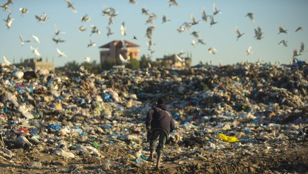 A Palestinian man runs as he collects plastic and other usable items at a garbage dump in Beit Lahia, in the northern Gaza strip, on February 19, 2017. (Photo by MAHMUD HAMS / AFP) - Sputnik International