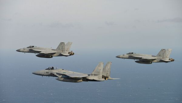 In this Nov. 10, 2017 photo provided by Japan Air Self-Defense Force, two of U.S. F/A-18, left, and right, and Japan Air Self-Defense Force's F-15 fly during a joint military exercise at an undisclosed location.  (Japan Air Self-Defense Force via AP) - Sputnik International