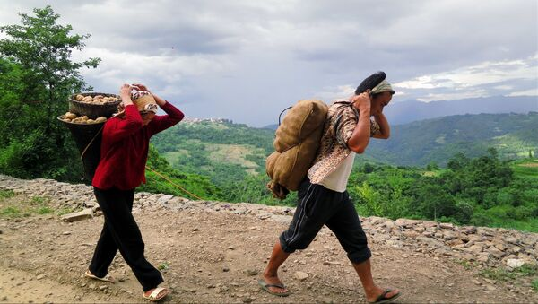 Nagas walk with basket loads of potatoes near Viswema village, in the northeastern Indian state of Nagaland (File) - Sputnik International