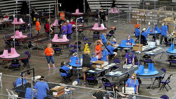 FILE - In this May 6, 2021 file photo, Maricopa County ballots cast in the 2020 general election are examined and recounted by contractors working for Florida-based company, Cyber Ninjas at Veterans Memorial Coliseum in Phoenix. For some conspiracy theorists, the 2020 election still hasn't ended. Trump supporters are pushing to re-examine ballots from November across the country, and finding success in swing states like Arizona and Georgia. Their efforts and sometimes misleading conclusions are being gleefully amplified by the former president. - Sputnik International