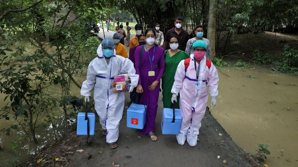 Healthcare workers carry COVISHIELD vaccine, a coronavirus disease (COVID-19) vaccine manufactured by Serum Institute of India, to inoculate villagers during a door-to-door vaccination and testing drive at Uttar Batora Island in Howrah district in West Bengal state, India, June 21, 2021 - Sputnik International