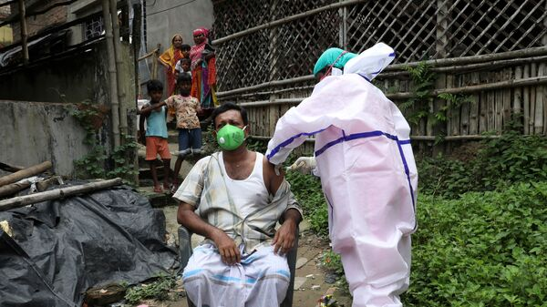 Yusuf Ali, a villager, receives a dose of COVISHIELD vaccine, a coronavirus disease (COVID-19) vaccine manufactured by Serum Institute of India, during a door-to-door vaccination and testing drive at Uttar Batora Island in Howrah district in West Bengal state, India, June 21, 2021 - Sputnik International
