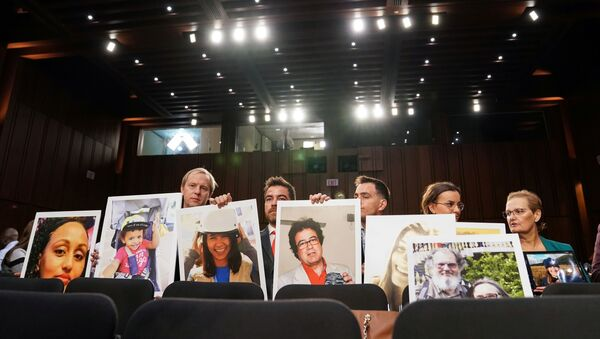 """Family members hold photographs of Boeing 737 MAX crash victims lost in two deadly 737 MAX crashes that killed 346 people as Boeing CEO Dennis Muilenburg testifies before a Senate Commerce, Science and Transportation Committee hearing on """"aviation safety"""" and the grounded 737 MAX on Capitol Hill in Washington, U.S., October 29, 2019 - Sputnik International"""