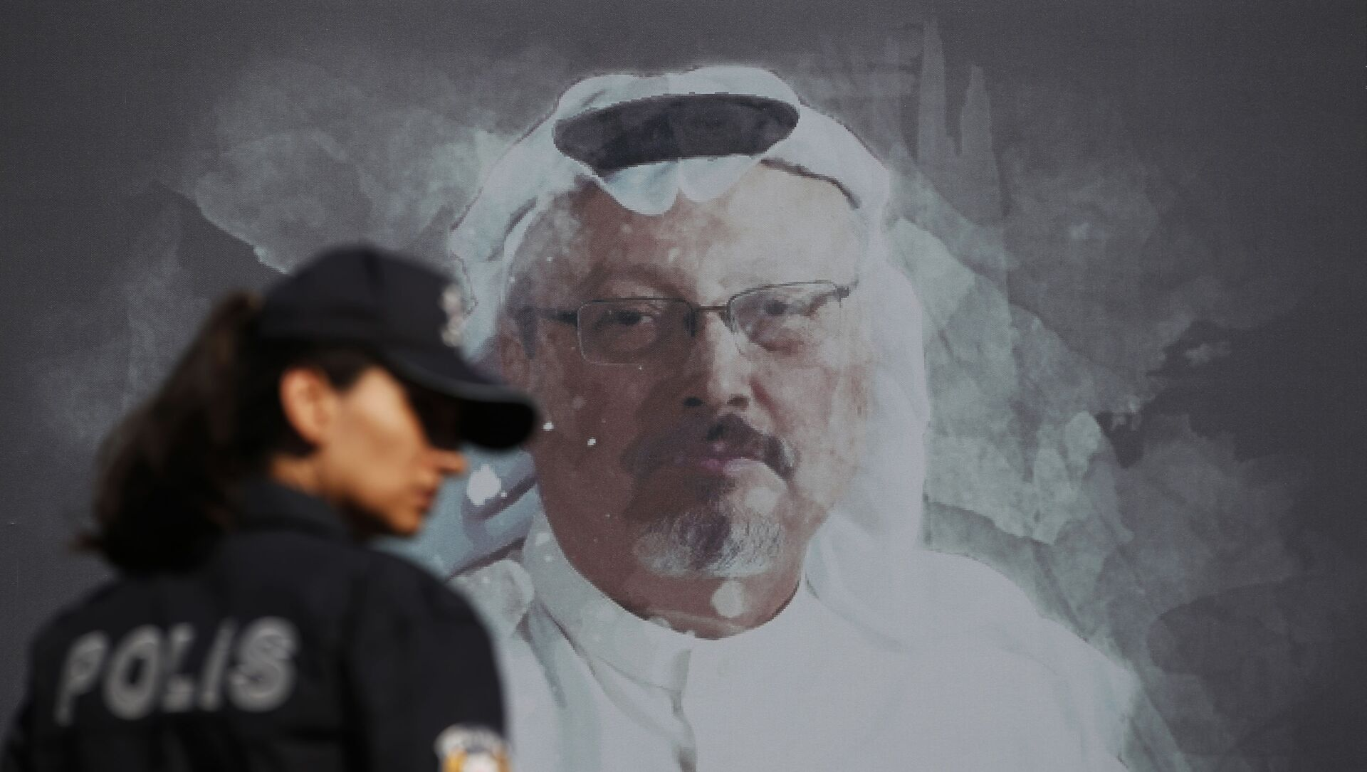 In this Wednesday, Oct. 2, 2019 file photo, a Turkish police officer walks past a picture of slain Saudi journalist Jamal Khashoggi prior to a ceremony, near the Saudi Arabia consulate in Istanbul, marking the one-year anniversary of his death. - Sputnik International, 1920, 03.08.2021