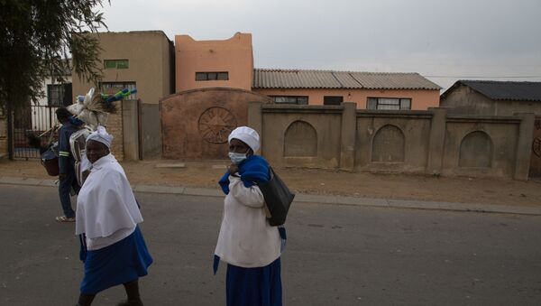 Neighbourhood woman passes the home, background, of Gosiame Thamara Sithole in Tembisa, near Johannesburg, Thursday, June 10, 2021. South Africa is gripped by a mystery over if the woman, Sithole, has, as has been claimed, given birth to 10 babies in what would be a world-first case of decuplets.  The South African government said Thursday it is still trying to verify the claim. - Sputnik International