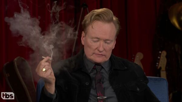 Screenshot captures the moment in which late-night host Conan O'Brien smokes a marijuana joint with sidekick Andy Richter and guest Seth Rogen. - Sputnik International