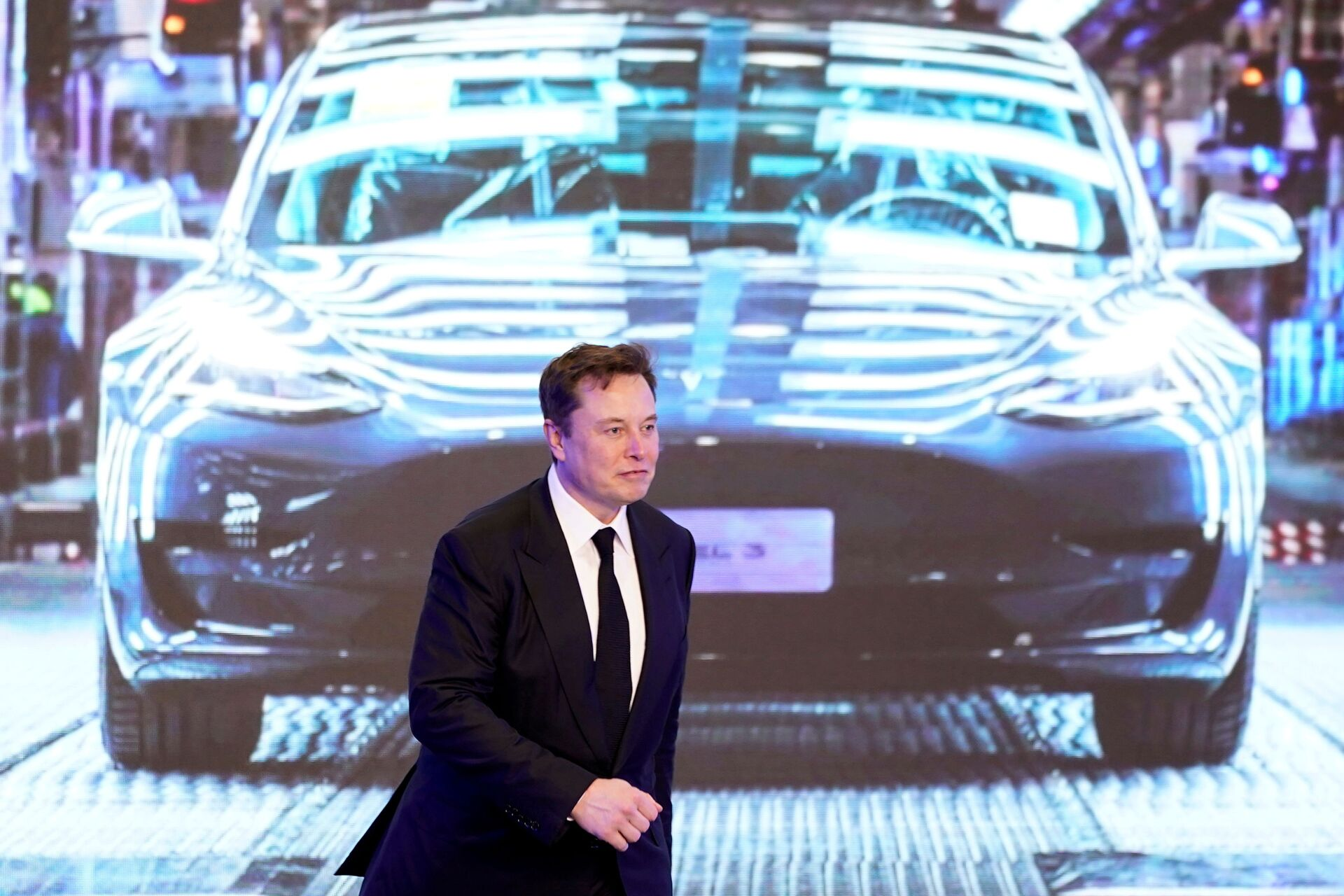 Tesla Inc CEO Elon Musk walks next to a screen showing an image of Tesla Model 3 car during an opening ceremony for Tesla China-made Model Y program in Shanghai, China January 7, 2020. - Sputnik International, 1920, 07.09.2021