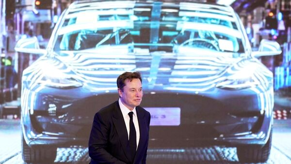 Tesla Inc CEO Elon Musk walks next to a screen showing an image of Tesla Model 3 car during an opening ceremony for Tesla China-made Model Y program in Shanghai, China January 7, 2020. - Sputnik International