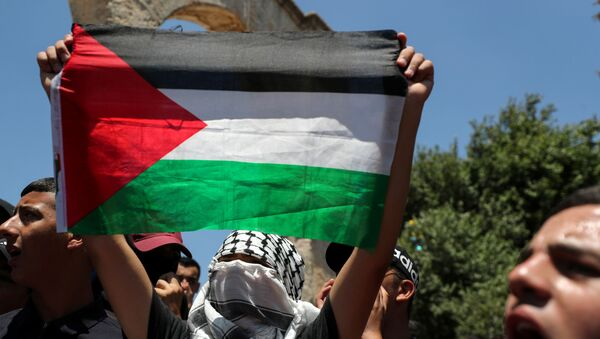 A demonstrator holds a Palestinian flag during a protest over the death of Nizar Banat, at the compound that houses Al-Aqsa Mosque, known to Muslims as Noble Sanctuary and to Jews as Temple Mount, in Jerusalem's Old City, June 25, 2021. - Sputnik International