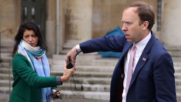 Britain's Health Secretary Hancock hands a microphone to his aide Coladangelo following a television interview outside BBC in London - Sputnik International
