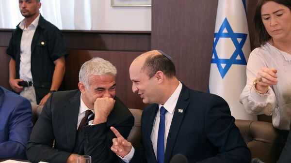 Israeli Prime Minister Naftali Bennett shares a joke with alternate Prime Minister and Foreign Minister Yair Lapid during the first weekly cabinet meeting of their new government in Jerusalem June 20, 2021. - Sputnik International