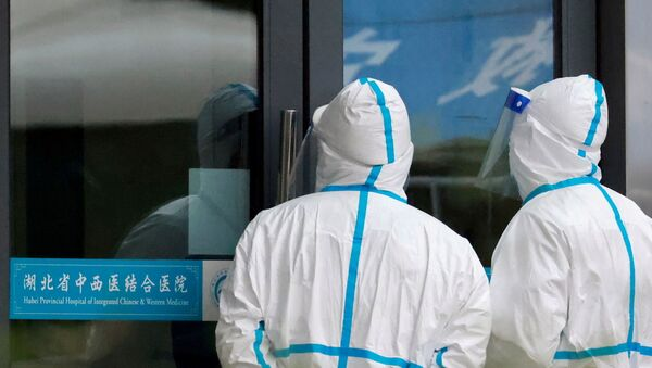 Staff members in protective suits stand at Hubei Provincial Hospital of Integrated Chinese and Western Medicine where members of the World Health Organization (WHO) team tasked with investigating the origins of the coronavirus disease (COVID-19) are visiting, in Wuhan, Hubei province, China January 29, 2021. - Sputnik International