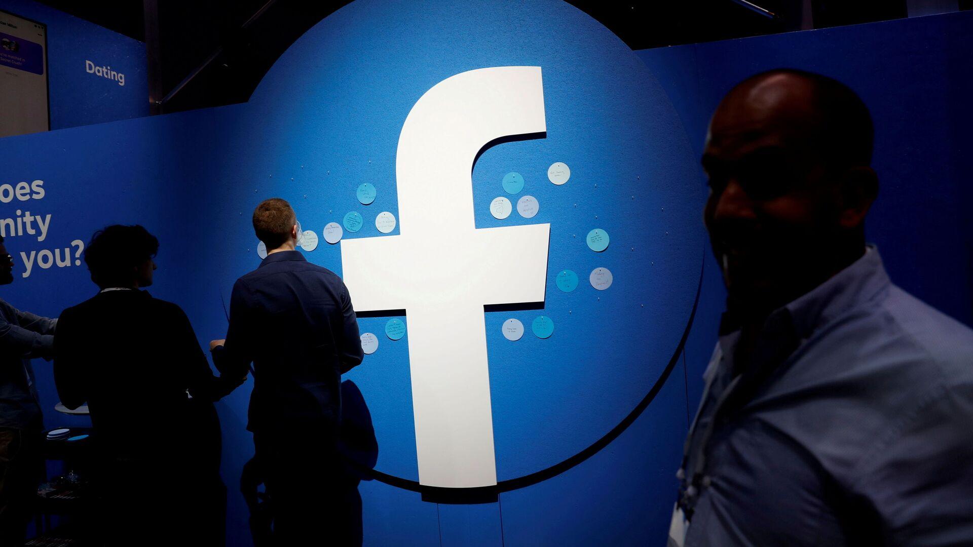 Attendees walk past a Facebook logo during Facebook Inc's F8 developers conference in San Jose - Sputnik International, 1920, 30.07.2021