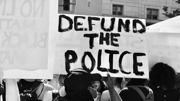Demonstrator at a George Floyd protest holding up a Defund the Police sign on June 5 2020 - Sputnik International