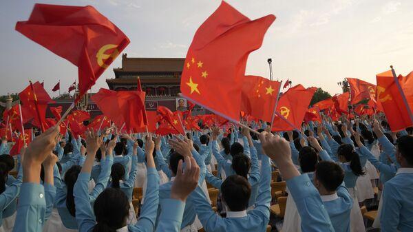 Участники праздновании 100-летия Коммунистической партии Китая с флагами в Пекине - Sputnik International