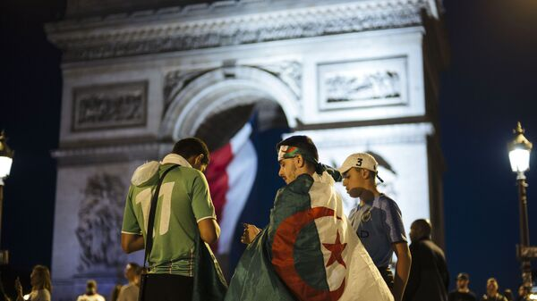 Algerians fans check their phones as the Arc de Triomphe is seen in the background after the African Cup of Nations semifinal soccer match between Algeria and Nigeria in Paris, France, Sunday, July 14, 2019.  - Sputnik International