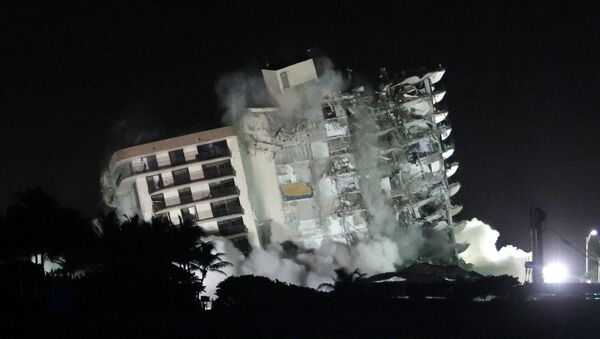The remaining part of the partially collapsed 12-story Champlain Towers South condo building falls with a controlled demolition on July 4, 2021 in Surfside, Florida. The decision by officials to bring the rest of the building down was brought on by the approach of Tropical Storm Elsa and fears that the structure might come down in an uncontrolled fashion. Over one hundred people are missing as the search-and-rescue effort continues. - Sputnik International