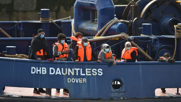 Waleed (3L), 29, a Kuwaiti migrant, stands with other migrants onboard the DHB Dauntless tug boat as they are brought to shore by the UK Border Force after illegally crossing the English Channel from France on a dinghy on September 11, 2020, in the marina at Dover, on the south coast of England - Sputnik International