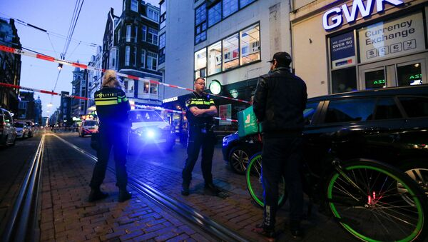 Police officers talk to a person as they stand guard in the area where Dutch celebrity crime reporter Peter R. de Vries, known for his reporting on some of the most renowned criminals in the Netherlands, was reportedly shot and seriously injured, in Amsterdam, Netherlands, July 6, 2021 - Sputnik International