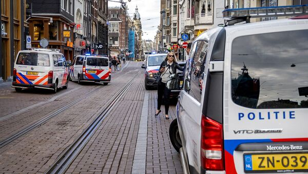 A woman walks past police vehicles parked on the site of an attack during which a Dutch journalist specialised in crime, Peter R. de Vries was seriously injured in a shooting in Amsterdam, on July 6, 2021. - Sputnik International