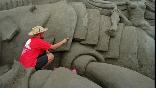 Wilfred Stijger, a sand sculptor from Holland, carves detail in a part of the The Lost City of Atlantis sand sculpture Monday Sept. 15, 1997 in San Diego - Sputnik International
