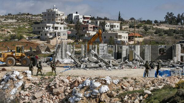 Israeli soldiers stand by as excavators demolish a Palestinian house (still under construction) located within the area C (where Israel retains full control over planning and construction) southeast of Hebron in the occupied West Bank on March 8, 2021. - Sputnik International