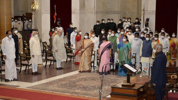 In this handout photo provided by the Indian Presidential Palace, the newly sworn in ministers, right, stand with Indian Prime Minister Narendra Modi, third left in front row, and other senior ministers during swearing in ceremony at the Presidential Palace in New Delhi, India, Wednesday, July 7, 2021. - Sputnik International