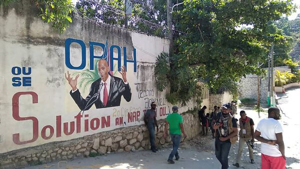 People walk past a wall with a mural depicting Haiti's President Jovenel Moise, after he was shot dead by unidentified attackers in his private residence, in Port-au-Prince, Haiti July 7, 2021.  - Sputnik International